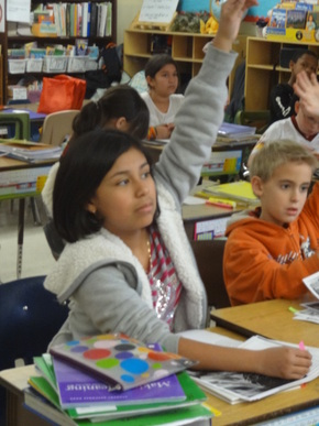 Washington District Elementary students raising their hand to answer a question.