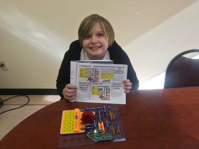 Here we have another proud 6th grader showing off his completed circuit project, which converts electrical energy into sound and light.